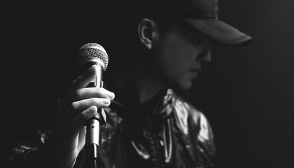 asian male singer hands on microphone, black and white