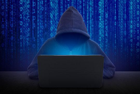 Hacker in front of his computer. Dark face.