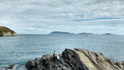 horizonte com vista para o mar com homens na rocha