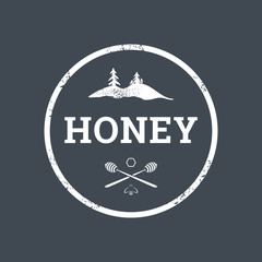 Vector logo template in the form of a circle for the production of natural honey in grunge style. Concept for organic farm products. EPS10. Illustration of crossed spoons for honey, bees, honeycomb an