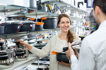Young cute positive  couple in the cookware section