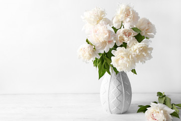 Vase with beautiful peonies on white background