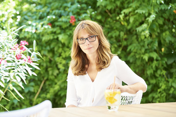 Beautiful smiling middle aged woman relaxing in the garden