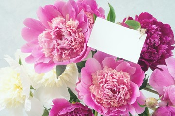 Bouquet of beautiful peonies with white blank tag. Closeup view, desaturated effect.