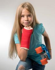 junges Mädchen mit gebrochenem Arm und Skateboard Blick in Kamera
