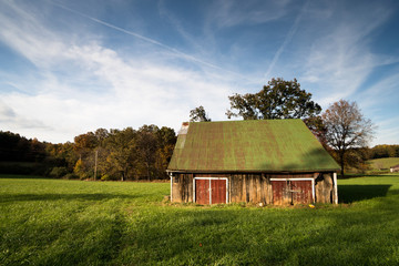 old abandoned barn on Skyline drive in Virginia on a beautiful fall day with a field and forest under a blue sky