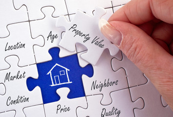 Property Value - female hand with real estate concept puzzle