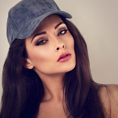 Beautiful sexy young make-up model with brown hair posing in blue baseball cap. Toned vintage closeup portrait