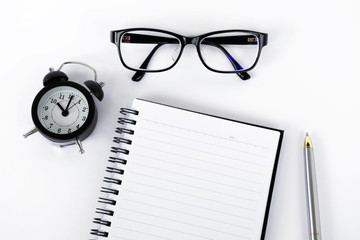 Blank notepad with eyeglasses, pen and alarm clock on white background