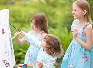 Three little sisters painting outdoors, having fun