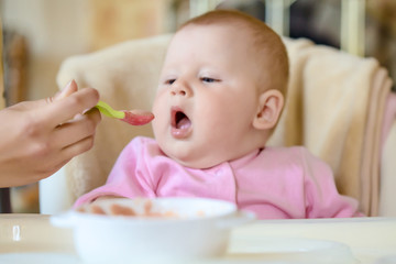 A cheerful happy child eats porridge.