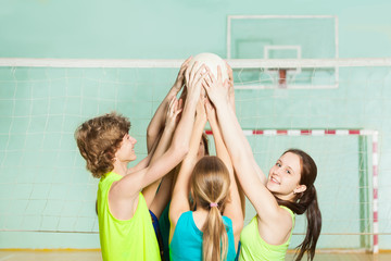 Teenage volleyball players holding ball overhead