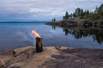 """Evening landscape of big lake with stone islands. In the foreground on a stone block, a """"Finnish candle"""" fire burns from a single log."""