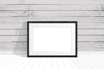Black photo frame on the floor near old painted wooden planks wall