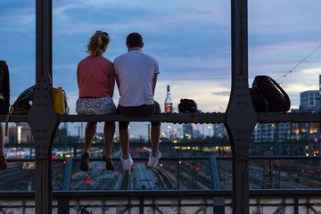 Young couple in love on romantic date sitting on railway bridge with a bottle of wine and watching the sunset over Munich urban city center. Just the two of us.