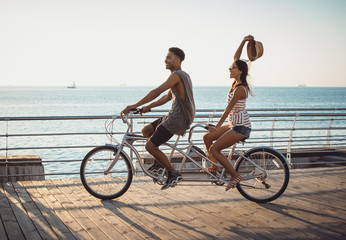 Portrait of a mixed race couple on tandem bicycle outdoors near the sea