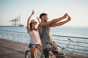 Portrait of a mixed race couple doing selfie on tandem bicycle outdoors near the sea