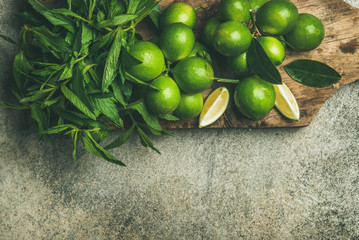Flatlay of freshly picked organic limes and mint leaves for making cocktail or lemonade on wooden rustic board over grey concrete stone background, top view, copy space