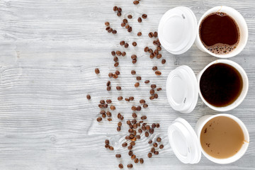 Coffee to go. Coffee cups with cover and coffee beans on wooden table backound top view copyspace