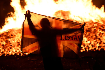 A man holds a Union flag in front of a bonfire in the Sandy Row area after it is lit by petrol bombs during the Twelfth of July celebrations held by members of Loyalist Orders in Belfast