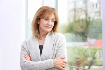 Attractive mature woman standing near window at home