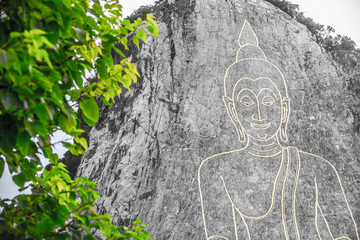 Golden Big Buddha on the mountain Khao Chi Chan, Pattaya, Thailand whit green leaf foreground