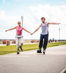 Active people friends rollerskating outdoor.