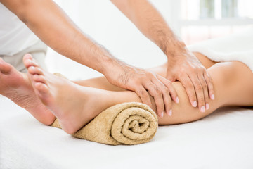 Hands of male therapist giving massage to a woman leg