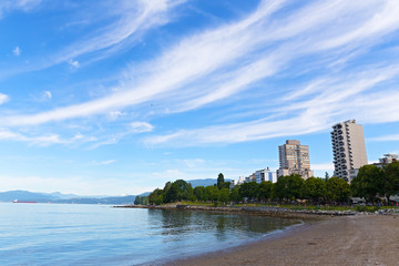 Vancouver urban landscape with a sandy sea beach and park, British Columbia, Canada. Summer in Vancouver with snow mountain peaks on horizon.