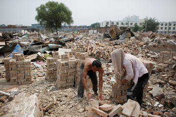 Workers pile up bricks left over after the demolition for former migrant worker dwellings on the outskirts of Beijing
