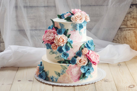 A beautiful home wedding three-tiered cake decorated with pink roses and blue flowers in a rustic style on wooden table