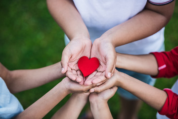 Close-up partial view of children holding red heart symbol outdoors