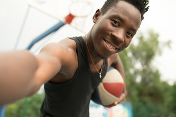 Portrait of african american man on basketball court make selfie