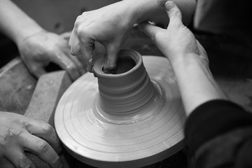 Hands working on a spinning pottery wheel, making pottery out of clay mud. close up photograph with a shallow depth of field.