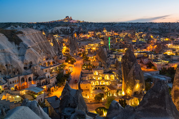 Ancient town and a castle of Uchisar dug from a mountains after twilight. Wall mural