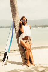 Sexy lady in sensual tunica on a tropical beach posing with surfboard near palm tree and look to camera. Happy modern hipster surfing girl have fun on sea ocean shore. Good sunny summer day for swim.