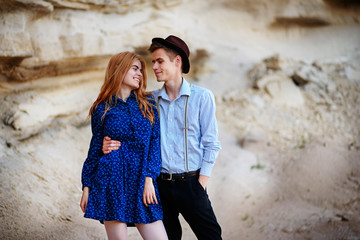 An attractive man hugs a beautiful woman in a blue dress in the middle of a sandy canyon. Lovers are happy, they are smiling to each other
