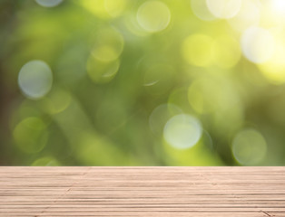 Wood table top on green bokeh background for product display montage.