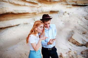 Attractive man and beautiful woman are looking at the screen of a smartphone on the background of a sand quarry