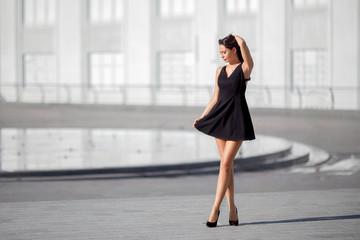 Woman in the black dress walking outdoor.