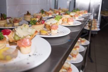 Many plates of appetizers being prepared in commercial kitchen, for an event