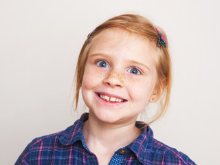 Portrait of funny redhead little girl smiling .