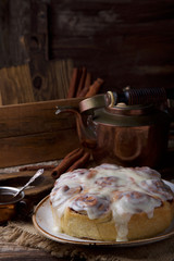 Glazed cinnabon buns on white craft plate with cup of coffee and cooper teapot on rustic wooden table opposite of wooden box with cinnamon sticks and wooden board