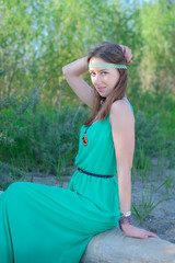 Beautiful girl hippie in a green dress sitting on a log