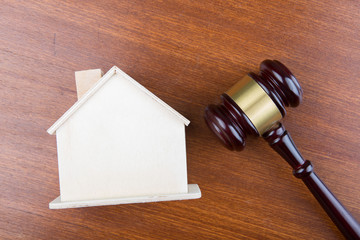 Real estate sale auction concept - gavel and house model on the wooden table