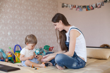 mother and little boy play with toys in the nursery