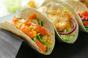 Stand with tasty fish tacos on dark table
