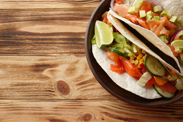 Plate with tasty fish tacos on wooden background