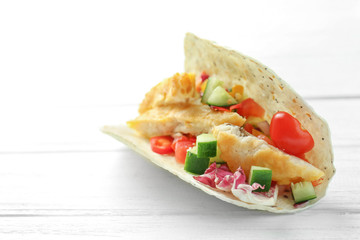 Tasty fish taco on white wooden background