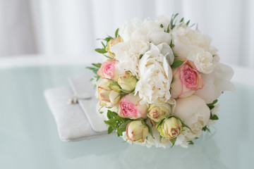 Bridal bouquet and purse on a light background